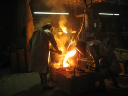 Workers casting metal in a foundry
