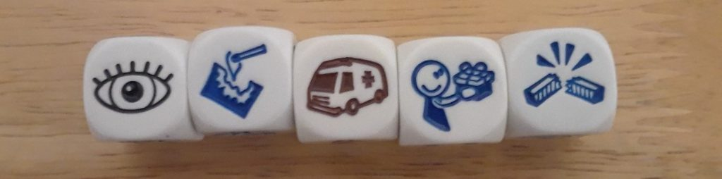 Five Story Cube dice in a row, showing an eye, a piece of paper being lit by a match, an ambulance, someone giving or receiving a gift, and a stick being broken.