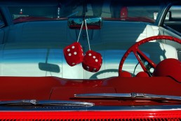 Old-fashioned fuzzy dice hanging from car mirror.